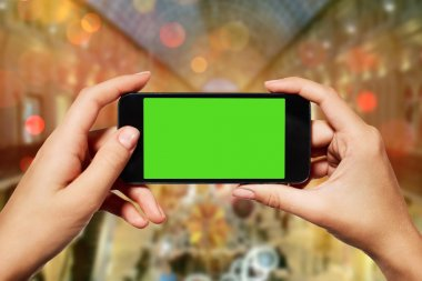isolated woman hand holding the smart phone with isolated green screen against Christmas or New Year shopping centre background with copy space.
