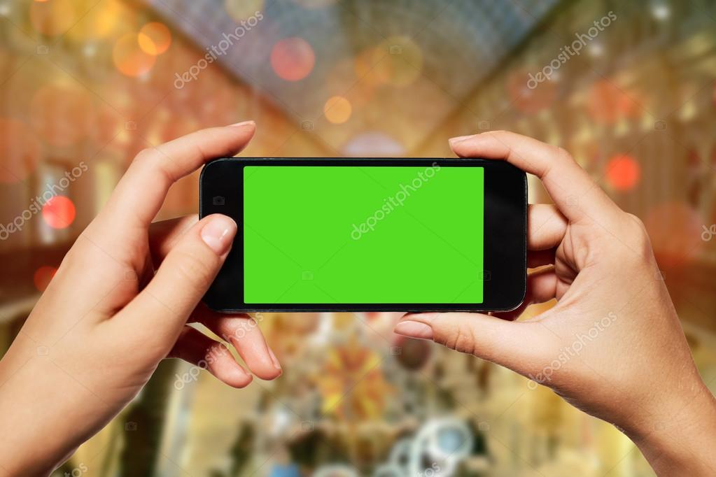 isolated woman hand holding the smart phone with isolated green screen against christmas or new year shopping centre background with copy space