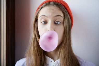 Beautiful and shocked or surprised young student girl blowing bubble from chewing gum.