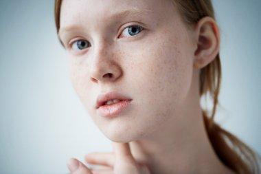 Beauty girl face Portrait. Beautiful model woman with freckles perfect fresh clean skin. Redhead female looking at camera. Youth and skin care concept. Isolated on background.