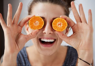 Young brunette woman holding tangerines instead of eyes, laughs and enjoys life. Harsh processing to emphasize the face structure. Human face expression body language reaction.