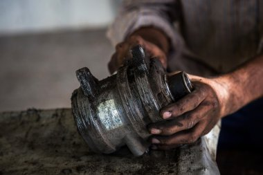 Worker at a Auto workshop cleaning the motor. Noise