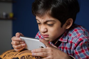 Angry Asian Child playing game on a smart phone.