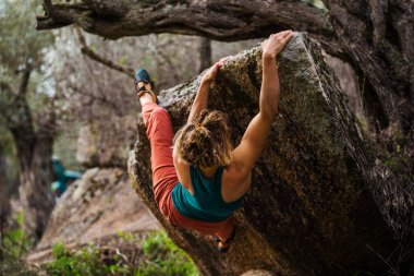 strong girl climbs bouldering on rocks. rock climbing in nature.