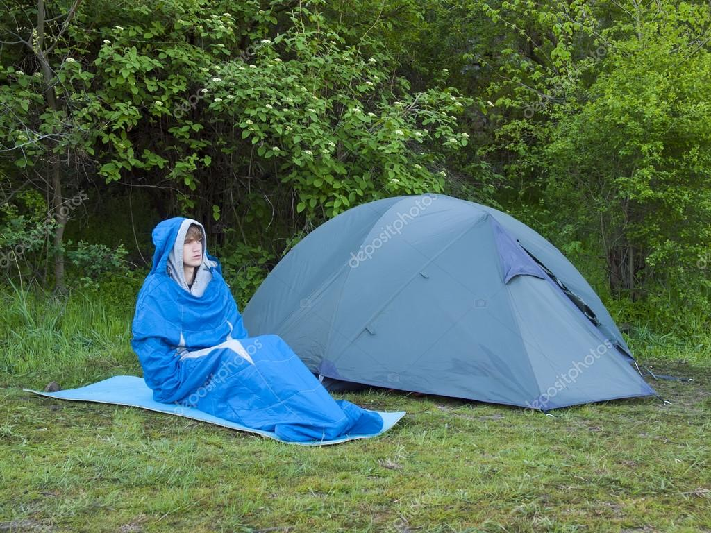 A man sits in a sleeping bag near the tent.