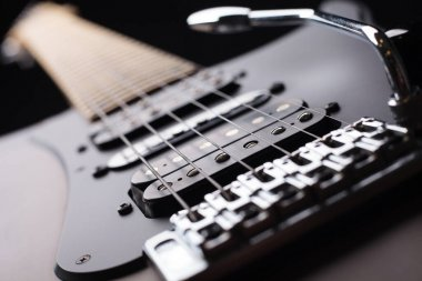 Elegant electric guitar on black background close up point of view showing from bridge silver saddles and humbucker pickups to neck head with silver tremolo