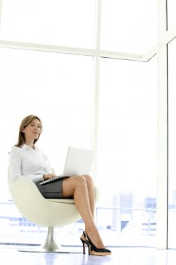 Businesswoman using laptop on knees