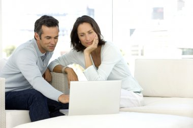Mature couple using laptop at home stock vector
