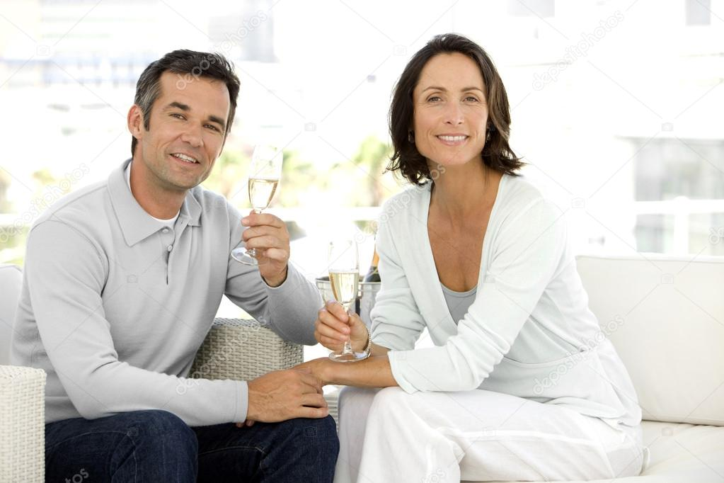 Middle-aged couple in love drinking Champagne