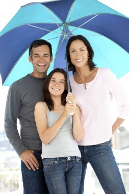Happy family with one kid under an umbrella