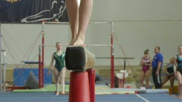 girl gymnast exercises on balance beam at gymnastics
