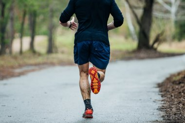 young male runner running on road in Park