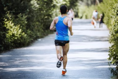Back view running male athlete