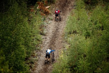two athlete mountainbiker walking with bicycle uphill