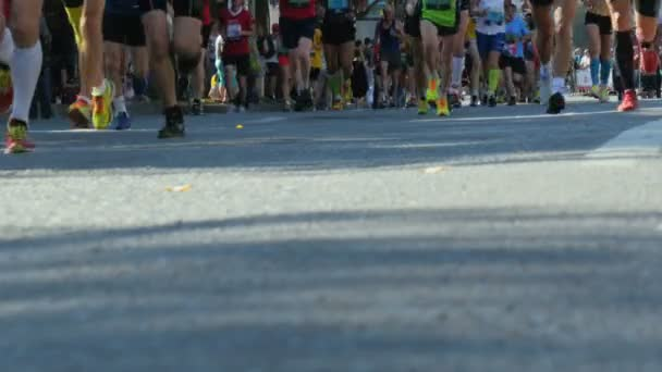 group of athletes marathon runners run through streets of city