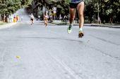 piedi uomini correre sulla strada asfaltata