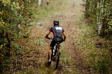 athlete racer mountainbike riding in autumn forest