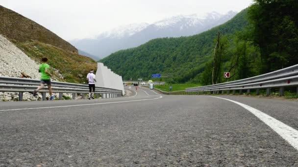 tři běžci běží horský maraton na dálnici