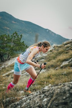 girl athlete with walking sticks going uphill