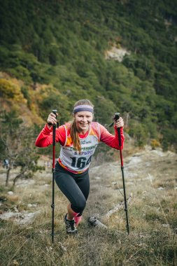 happy girl athlete climbs a mountain with nordic walking poles