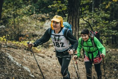 family athletes climb uphill on forest trail