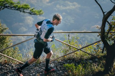 young athlete running down mountain path along fence