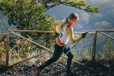 young woman athlete running on mountain trail with nordic walking poles