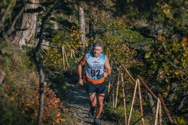 male athlete senior years runs on a mountain trail