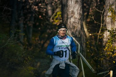 young male athlete in headband and glasses runs along Hiking trail