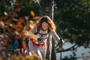 closeup of young woman with Hiking sticks. autumn landscape