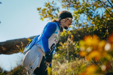 closeup of young male athlete in headband and glasses. autumn landscape