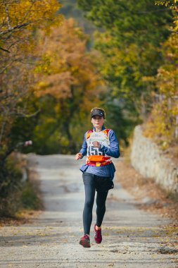 young woman runs across road in autumn forest