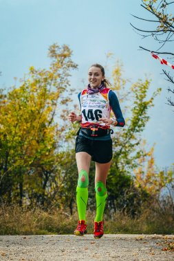 girl running on road in autumn forest in compression socks and kinesio tape on knees
