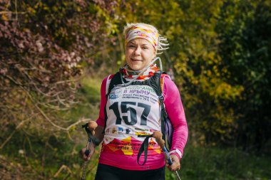 blonde middle-aged woman runs through autumn forest with nordic walking poles