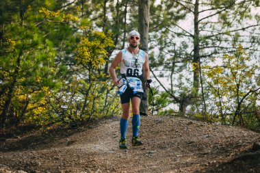 young male runner running through forest trail with nordic walking poles