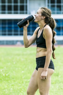 Beautiful girl athlete drinking water