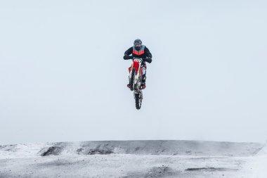 motocross rider jumping over mountain