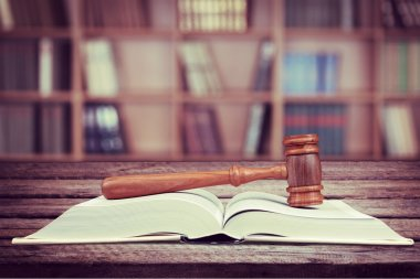 wooden judge gavel and book