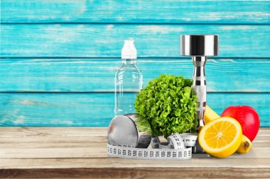 dumbbells with  water , measuring tape and fruits