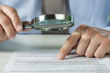 Businessman with report using a magnifying glass.