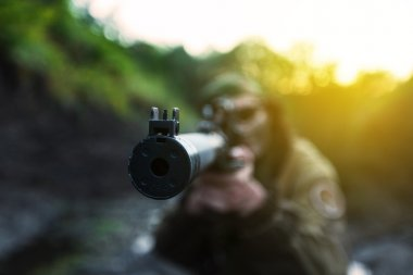 Woman soldier aiming, focus on muzzle