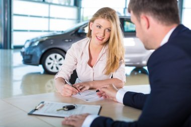 happy woman with car dealer