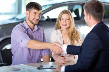 happy couple with car dealer
