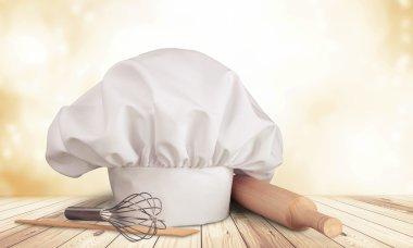 White cooks cap and kitchen utensils