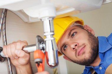 Plumber hands fixing water tap