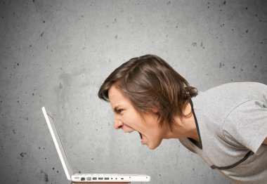 young man screaming on laptop