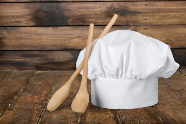 White cooks cap and wooden spoons