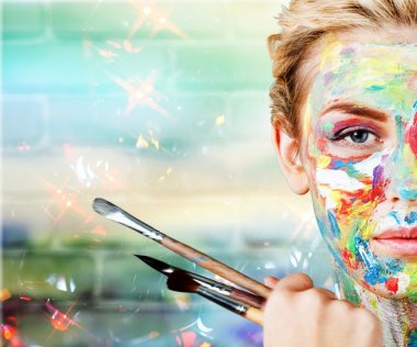 woman with painted  face and paintbrushes