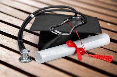 graduation hat , diploma with stethoscope