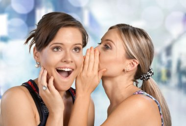 Woman revealing secret to her friend